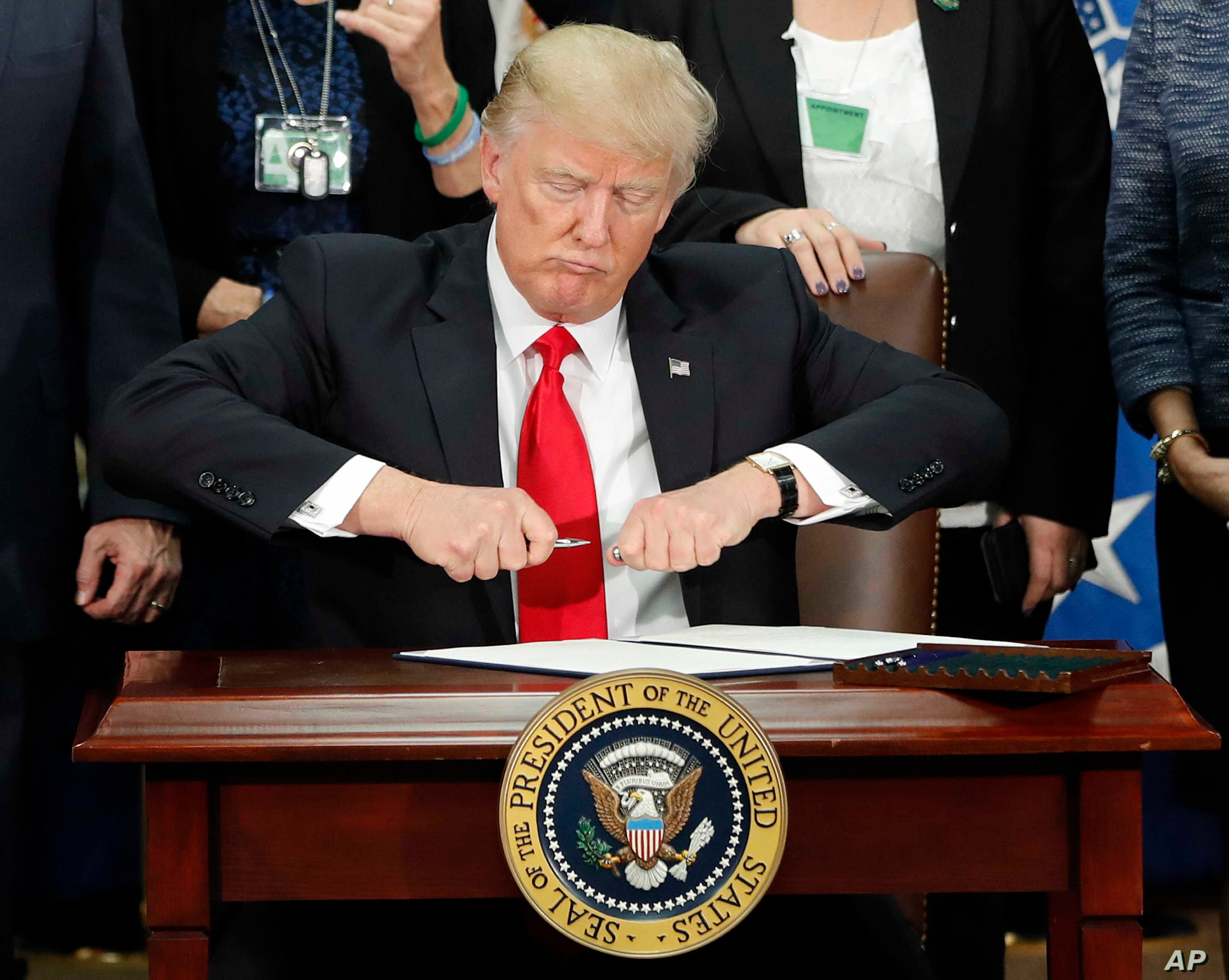 DAY 6 - In this Jan. 25, 2017, file photo, President Donald Trump takes the cap off a pen before signing executive order for immigration actions to build border wall during a visit to the Homeland Security Department in Washington. (AP Photo/Pablo Martinez Monsivais, File)